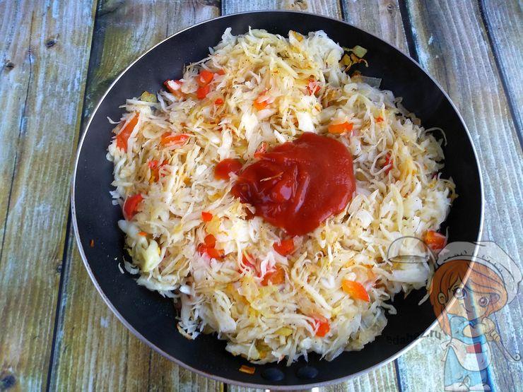 Выкладываем в сковороду капусту и добавляем томатную пасту
